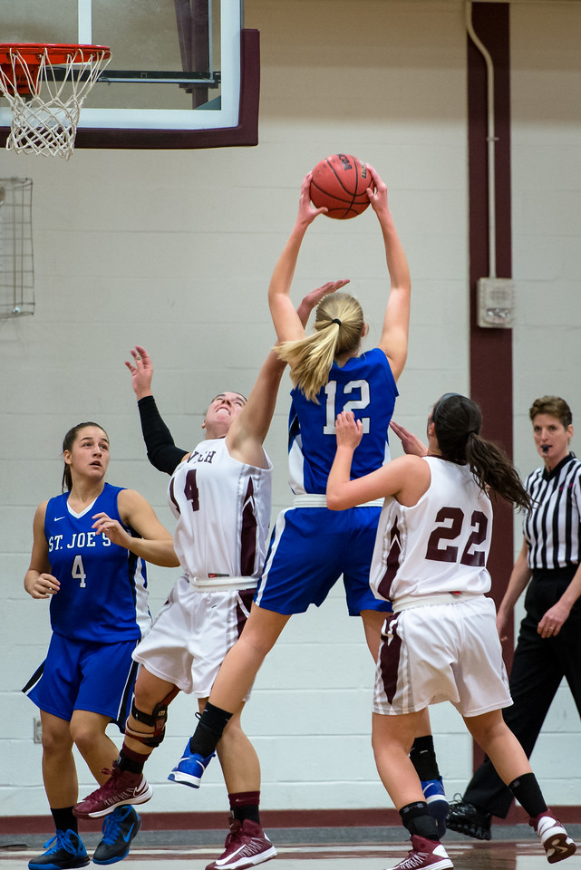 Abby Young (12) pulls down a rebound as Skyler Makkinje (4) looks on during the Women's Basketball game between Saint Joseph's (ME) and Norwich University at Norwich University, Northfield, Vermont, USA on January 05, 2013. Photo: Chris Poss