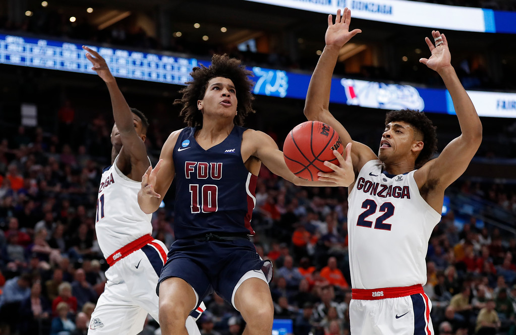 . Fairleigh Dickinson guard Brandon Powell (10) drives between Gonzaga guard Joel Ayayi (11) and forward Jeremy Jones (22) during the second half of a first-round game in the NCAA men�s college basketball tournament Thursday, March 21, 2019, in Salt Lake City. (AP Photo/Jeff Swinger)