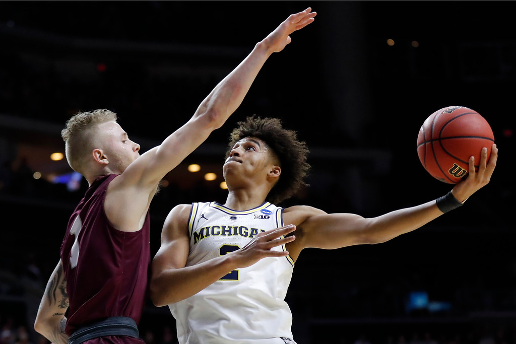 . Michigan guard Jordan Poole shoots over Montana guard Timmy Falls, left, during a first round men\'s college basketball game in the NCAA Tournament, Thursday, March 21, 2019, in Des Moines, Iowa. (AP Photo/Charlie Neibergall)