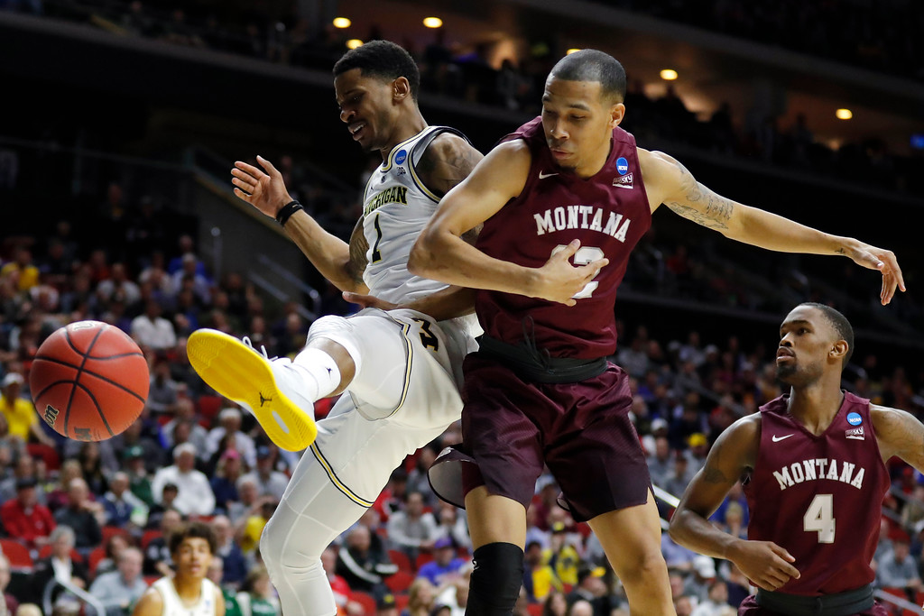 . Michigan guard Charles Matthews, left, fights for a loose ball with Montana\'s Kendal Manuel and Sayeed Pridgett (4) during a first round men\'s college basketball game in the NCAA Tournament, Thursday, March 21, 2019, in Des Moines, Iowa. (AP Photo/Charlie Neibergall)