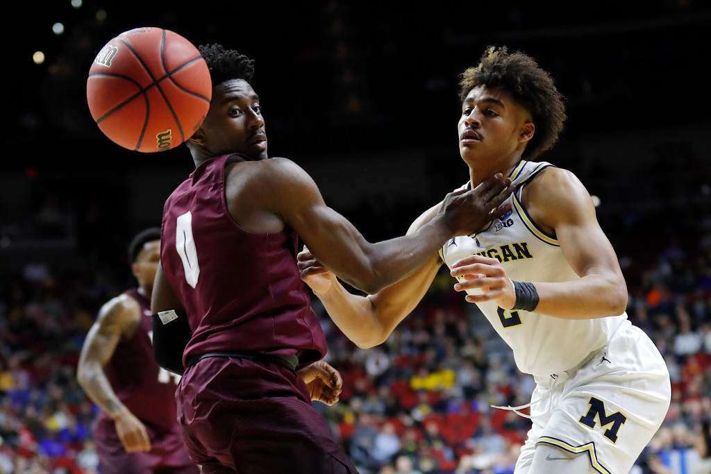 . Michigan guard Jordan Poole looses the ball out of bounds in front of Montana guard Michael Oguine, left, during a first round men\'s college basketball game in the NCAA Tournament, Thursday, March 21, 2019, in Des Moines, Iowa. (AP Photo/Charlie Neibergall)