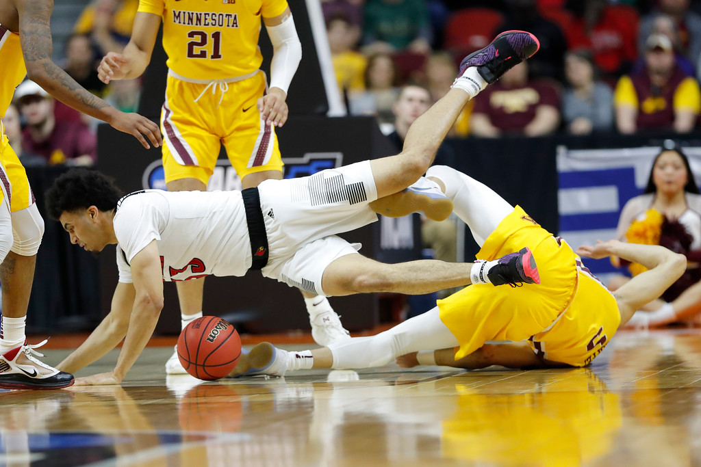 . Louisville forward Jordan Nwora is fouled by Minnesota guard Amir Coffey, right, during a first round men\'s college basketball game in the NCAA Tournament, Thursday, March 21, 2019, in Des Moines, Iowa. (AP Photo/Charlie Neibergall)