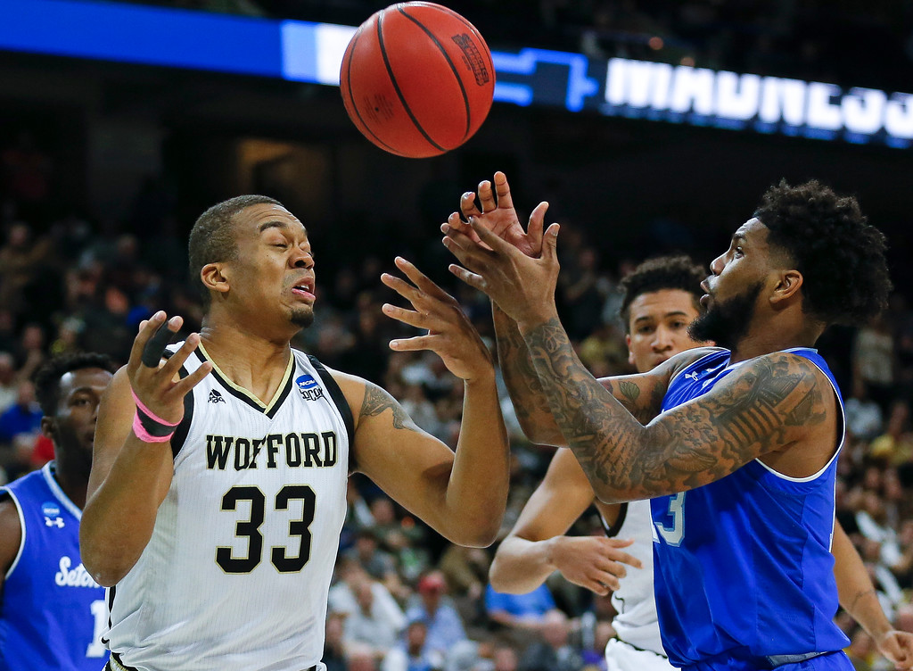 . Wofford\'s Cameron Jackson (33) and Seton Hall\'s Myles Powell, right, go after a loose ball during the first half of a first-round game in the NCAA men�s college basketball tournament in Jacksonville, Fla., Thursday, March 21, 2019. (AP Photo/Stephen B. Morton)