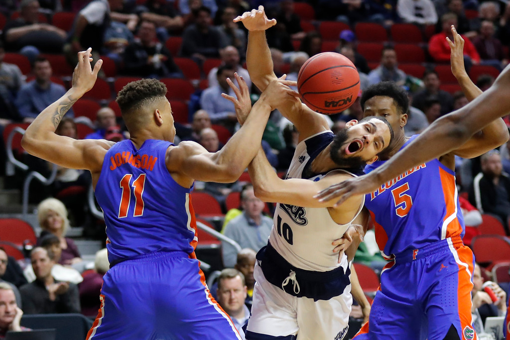 . Nevada forward Caleb Martin, center, loses the ball while driving between Florida\'s Keyontae Johnson, left, and KeVaughn Allen, right, during a first round men\'s college basketball game in the NCAA Tournament, Thursday, March 21, 2019, in Des Moines, Iowa. (AP Photo/Charlie Neibergall)
