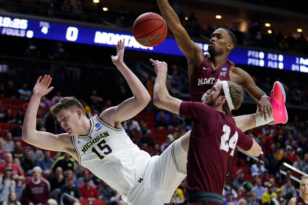 . Michigan center Jon Teske (15) is fouled while driving to the basket in front of Montana guard Bobby Moorehead (24) and Sayeed Pridgett, rear, during a first round men\'s college basketball game in the NCAA Tournament, Thursday, March 21, 2019, in Des Moines, Iowa. (AP Photo/Charlie Neibergall)