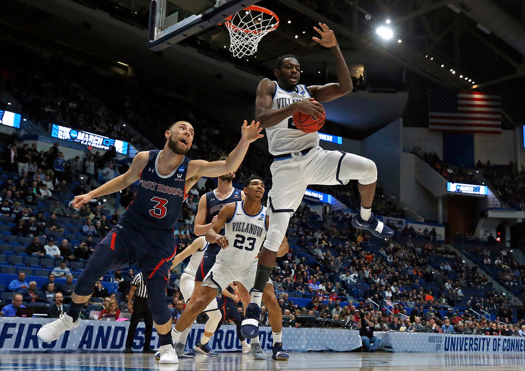 . Villanova\'s Dhamir Cosby-Roundtree (21) blocks a shot and grabs the ball from St. Mary\'s Jordan Ford (3) during the first half of a first round men\'s college basketball game in the NCAA Tournament, Thursday, March 21, 2019, in Hartford, Conn. (AP Photo/Elise Amendola)
