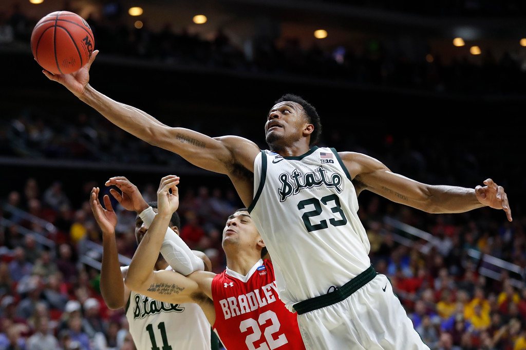 . Michigan State forward Xavier Tillman (23) grabs a rebound over Bradley guard Ja\'Shon Henry (22) during a first round men\'s college basketball game in the NCAA Tournament, Thursday, March 21, 2019, in Des Moines, Iowa. (AP Photo/Charlie Neibergall)