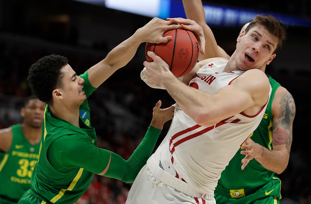 . Wisconsin forward Ethan Happ, right, is defended by Oregon guard Will Richardson, left, and forward Paul White, rear, during the first half of a first-round game in the NCAA men�s college basketball tournament Friday, March 22, 2019, in San Jose, Calif. (AP Photo/Ben Margot)