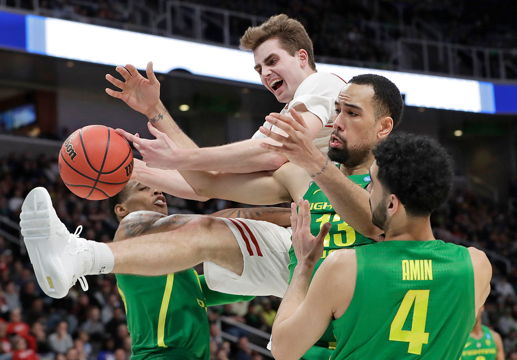 . Wisconsin forward Nate Reuvers, top, reaches for a rebound over Oregon forward Paul White, second from right, and guard Ehab Amin (4) during the second half a first-round game in the NCAA men�s college basketball tournament, Friday, March 22, 2019, in San Jose, Calif. (AP Photo/Chris Carlson)