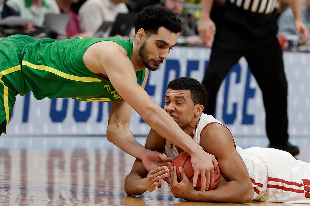 . Wisconsin guard D\'Mitrik Trice, bottom, holds onto the ball under Oregon guard Ehab Amin during the first half of a first-round game in the NCAA men�s college basketball tournament, Friday, March 22, 2019, in San Jose, Calif. (AP Photo/Chris Carlson)