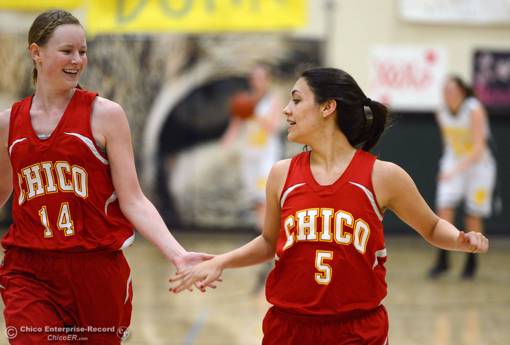 . Chico High\'s #14 Lindsey Lundberg (left) high-fives #5 Sarah Seibert (right) on a basket against Paradise High in the second quarter of their girls basketball game at PHS Tuesday, February 18, 2014 in Paradise, Calif.  (Jason Halley/Chico Enterprise-Record)