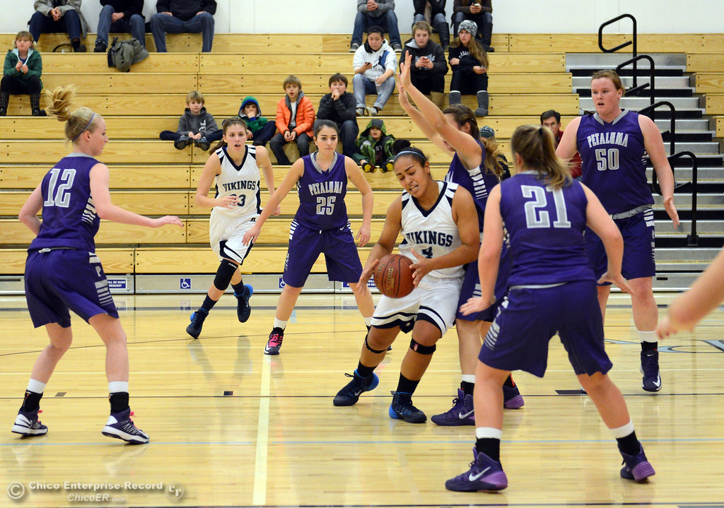 . Pleasant Valley High\'s #4 Dominique Jackson (center) drives to the basket against Petaluma High in the first quarter of their girls basketball game at PVHS Varley Gym Friday, December 6, 2013 in Chico, Calif. (Jason Halley/Chico Enterprise-Record)