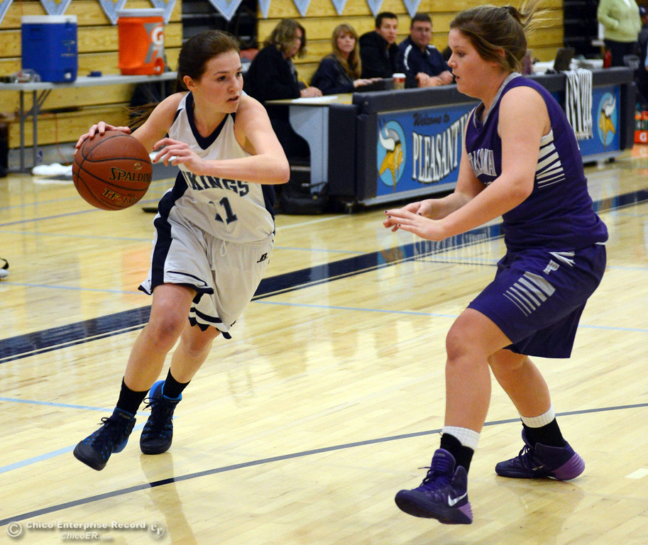 . Pleasant Valley High\'s #11 Kristina Joyce (left) dribbles against Petaluma High\'s #21 Cassie Baddeley (right) in the first quarter of their girls basketball game at PVHS Varley Gym Friday, December 6, 2013 in Chico, Calif. (Jason Halley/Chico Enterprise-Record)