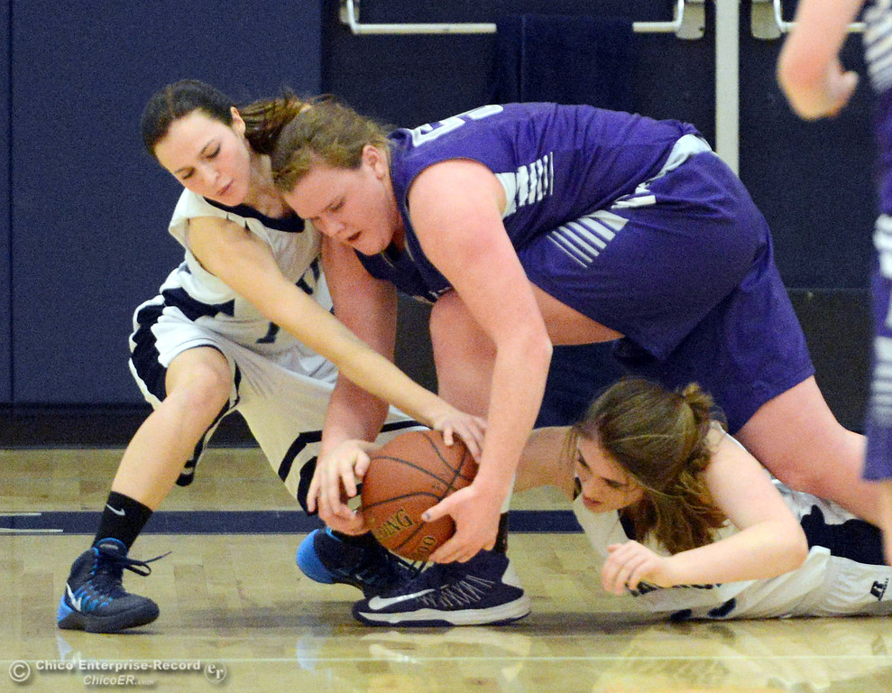 . Pleasant Valley High\'s #14 Kayla Joyce (left) and #25 Courtney Holloway (right) battle for a loose ball against Petaluma High\'s #50 Allison Scranton (center) in the first quarter of their girls basketball game at PVHS Varley Gym Friday, December 6, 2013 in Chico, Calif. (Jason Halley/Chico Enterprise-Record)