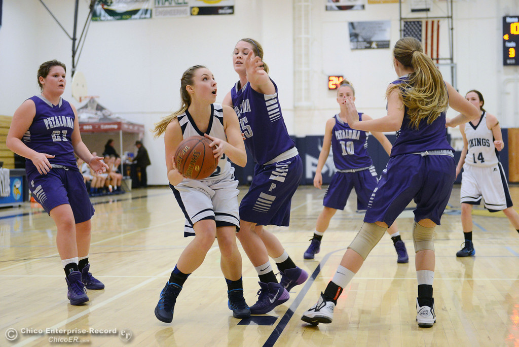 . Pleasant Valley High\'s #22 Ashely Geiger (left) dribbles against Petaluma High\'s #35 Maddie Mehciz (center) in the first quarter of their girls basketball game at PVHS Varley Gym Friday, December 6, 2013 in Chico, Calif. (Jason Halley/Chico Enterprise-Record)