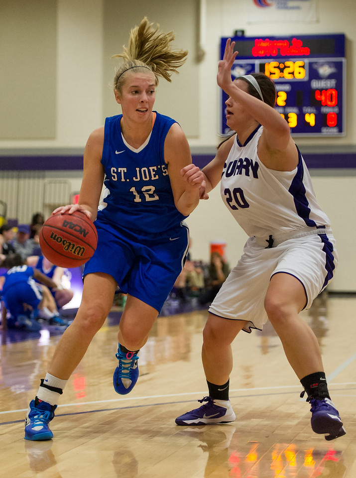 Abby Young (12) drives toward the basket during the Women's Basketball game between Saint Joseph's (ME) and Curry Collage at Curry College, Milton, Massachusetts, USA on November 16, 2013. Photo: Chris Poss