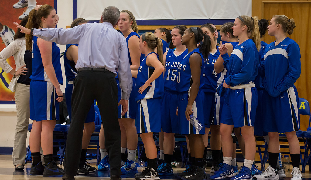 Head Coach Mike McDevitt talks with the team during a timeout during the Women's Basketball game between Saint Joseph's (ME) and Maine Maritime Academy at Maine Maritime Academy, Castine, Maine, USA on November 23, 2013. Photo: Chris Poss