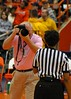 The officials used pink whistles in support of it being Breast Cancer Awareness day in women's collegiate sports.  The photographer surprised this official by wanting her picture during a time out with the whistle.