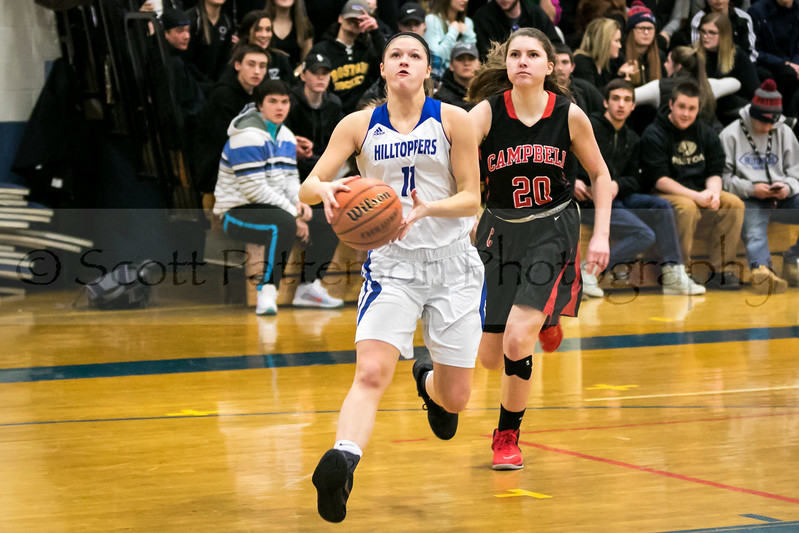 Somersworth's Sylvia Hamilton, left, slips by the defense of Cambpell's Caedran Sullivan, right, while driving to the hoop during Division III basketball action in Somersworth Friday. [Photo by Scott Patterson/Fosters.com]