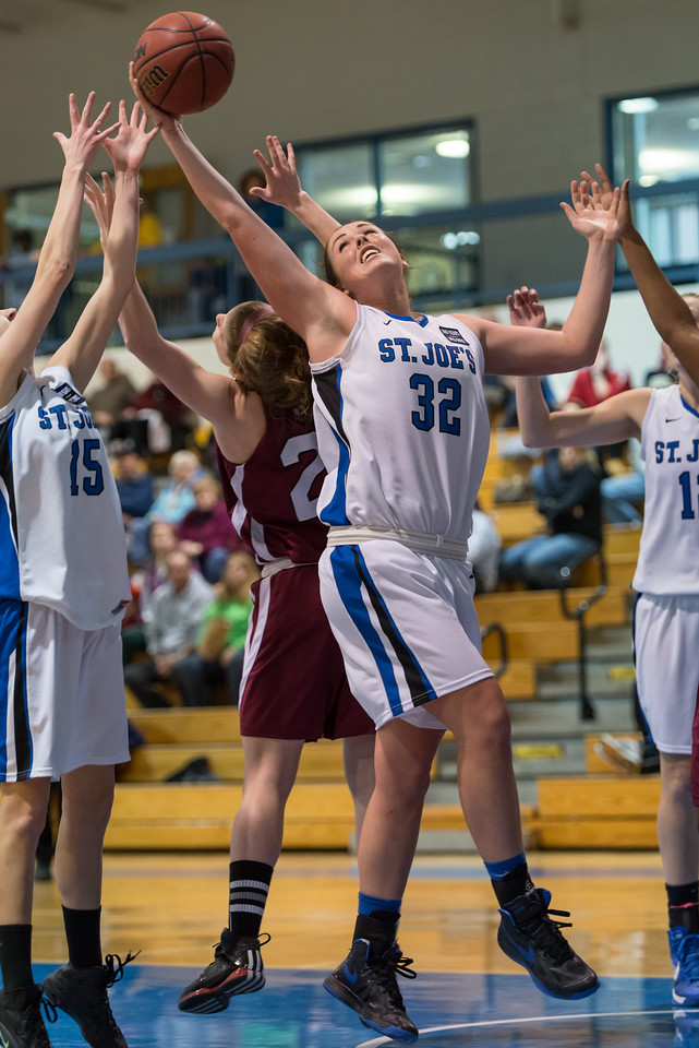 Morgan Cahill (32) retrieves a rebound as Danyelle Shufelt (15) and Abby Young (12) look on during the Women's Basketball game between Saint Joseph's (ME) and Anna Maria College at Saint Joseph's College, Standish, Maine, USA on January 19, 2013. Photo: Chris Poss