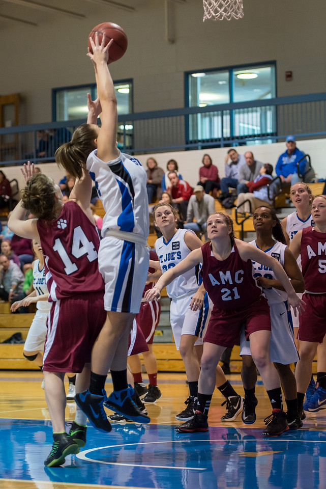 Skyler Makkinje (4) pulls down a rebound as Lindsay Moore (22), Sarah Assante (20), Abby Young (12) and Alyssa Grigware (11) look on during the Women's Basketball game between Saint Joseph's (ME) and Anna Maria College at Saint Joseph's College, Standish, Maine, USA on January 19, 2013. Photo: Chris Poss