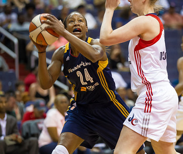 Tamika Catchings of the Indiana Fever drives past Emma Meesseman of the Washington Mystics