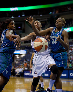 Washington Mystics Chasity Melvin goes up between Charde Houston and Nicky Anosike of the Minnesota Lynx in a WNBA match at the Verizon Center in Washington DC on August 13, 2010. The Washington Mystics defeated the Minnesota Lynx 61-58. Melvin scored 9 points in the game. (Photo by Jeff Malet)