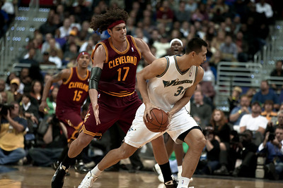 Yi Jianlian of the Washington Wizards is guarded by Anderson Varejao of the Cleveland Cavaliers.