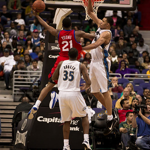 Thaddeus Young of the Philadelphia 76ers goes up strong to the basket against Trevor Booker and JaVale McGee of the Washington Wizards.