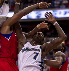Andray Blatche of the Washington Wizards takes a hand to the face from Marreese Speights  of the Philadelphia 76ers under the basket during overtime.