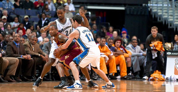 Daniel Gibson of the Cleveland Cavaliers is tied up by Kirk Hinrich and Hilton Armstrong of the Washington Wizards.
