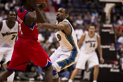 Gilbert Arenas of the Washington Wizards guards Jrue Holiday of the Philadelphia 76ers.