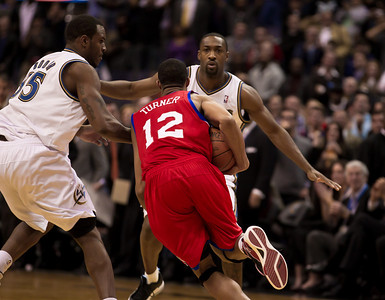 Evan Turner of the Philadelphia 76ers drives past Trevor Booker and Gilbert Arenas of the Washington Wizards during overtime.