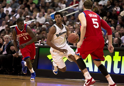 Nick Young of the Washington Wizards dribbles between Jrue Holiday and Andres Nocioni of the Philadelphia 76ers.