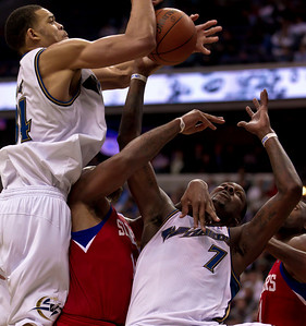 JaVale McGee goes high for the ball while teammate Andray Blatche of the Washington Wizards takes a hand to the face from Marreese Speights of the Philadelphia 76ers under the basket during overtime.