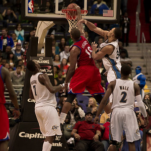 Marreese Speights of the Philadelphia 76ers goes up for a slam dunk over JaVale McGee of the Washington Wizards.