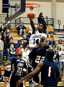 South Cobb's Richard Connor (23), Ant Davis (22), and Donterius Sutton (1) can do nothing but watch as Marietta's Barrington Ferguson (14) completes a dunk against them Tuesday night.