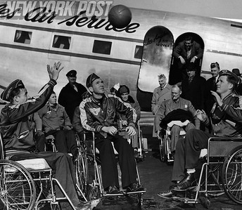 Paralyzed Veterans throw around a basketball in front of Los Angeles airplane. 1948