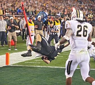 Bryce Petty makes a touchdown as he flies upside down thru the air doing a flip as a result of a defensive hit at the goal line.