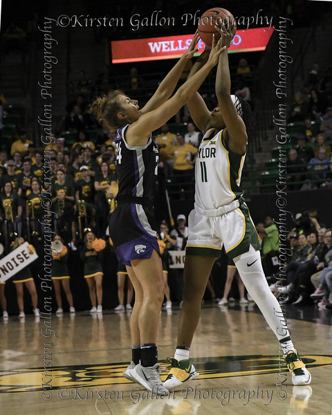 Baylor guard Jordyn Oliver tries to pass the ball over the hands of Kansas State guard Emilee Ebert.