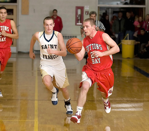Record-Eagle/Keith King<br /> Suttons Bay's Noah Reyhl, right, drives with the ball against Traverse City St. Francis' Nick Clear Friday, December 10, 2010 at Traverse City St. Francis High School.