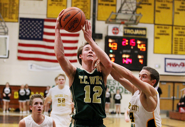 Record-Eagle/Keith King<br /> Traverse City West's Jeremiah Williams (12) is fouled by Traverse City Central's Nate Schlusler (24) Thursday, January 17, 2013 at Traverse City Central High School.
