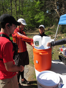 Volunteer coordinator (Ken) shows Trilife friends Gerry and C(ynthina)-Lo how to mix Gu Brew