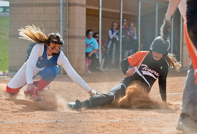 Pitcher Kassidy Whitney #11 tries to tag out Lainey Davis #13 at home plate.  At Ogden High School on April 7, 2015.