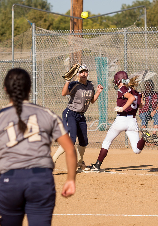 . Berthoud\'s Sedona Cook (9) beats a throw to Frederick first baseman Grace Brunstrom (15) Thursday afternoon Sept. 29, 2016 on the Spartans home field in Berthoud. (Photo by Michael Brian/Loveland Reporter-Herald)