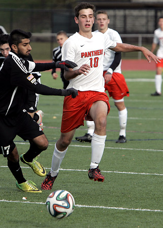 KEN YUSZKUS/Staff photo. Beverly's Savio Polini, right, runs after the ball along with a Winchester player during the Winchester at Beverly boys soccer in Division 2 North playoff quarterfinals.   11/7/14