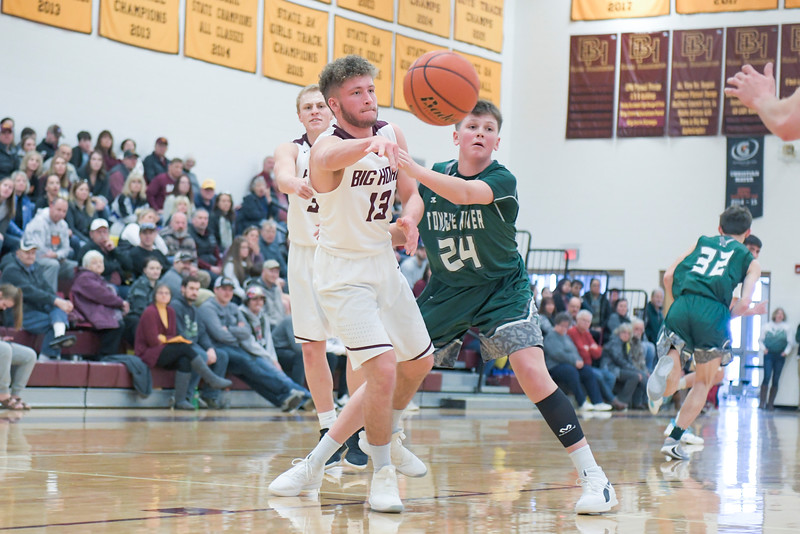 Ashleigh Snoozy | The Sheridan Press<br>Big Horn's Garrett Custis (13) passes to a teammate as Tongue River's Cade Reish (24) guards him at Big Horn High School Saturday, Jan. 18, 2020.