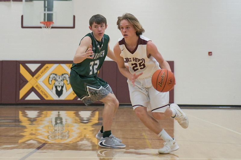 Ashleigh Snoozy | The Sheridan Press<br>Tongue River's Eli Cummins (32) guards Big Horn's Ayden Phillips (25) as he dribbles down the court Saturday, Jan. 18, 2020.