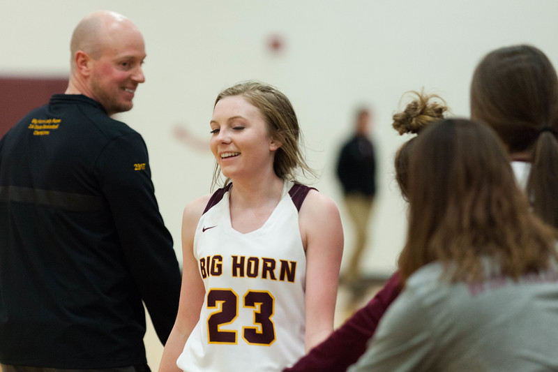 Tibby McDowell | The Sheridan Press<br /> <br /> Jordan Frank (23) shares a laugh with head coach Michael McGuire, left, as she comes off the court in the fourth quarter at Big Horn High School Friday Feb 2, 2018.  The Lady Rams handily beat the Wolves 46-29.