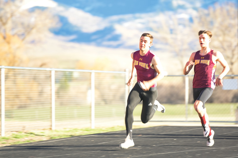 Matthew Gaston | The Sheridan Press<br>Big Horn's Kyler Ostler takes the hand off from Liam Greenelsh during the 400-meter relay Thursday, April 18, 2019.